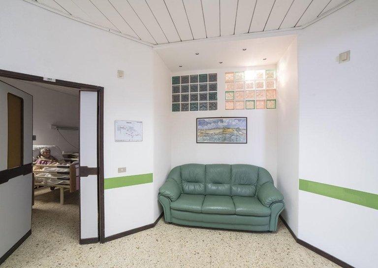 vista frontale di un divano con attrezzatura su parete a Casa Riposo SANATRIX