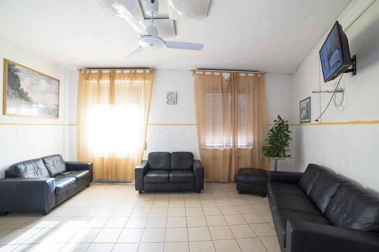 vista interna di un soggiorno con divani neri, tende trasparente, televisione e pavimento in piastralle