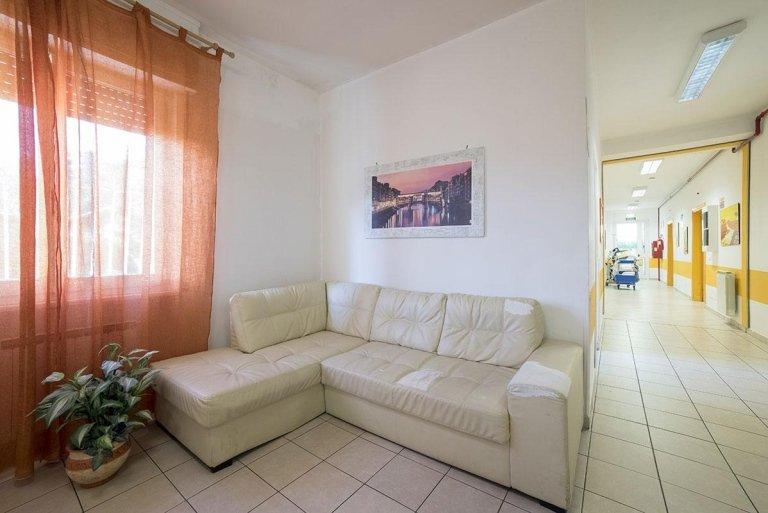vista di corridoio e una stanza con divano, vaso e tenda trasparente
