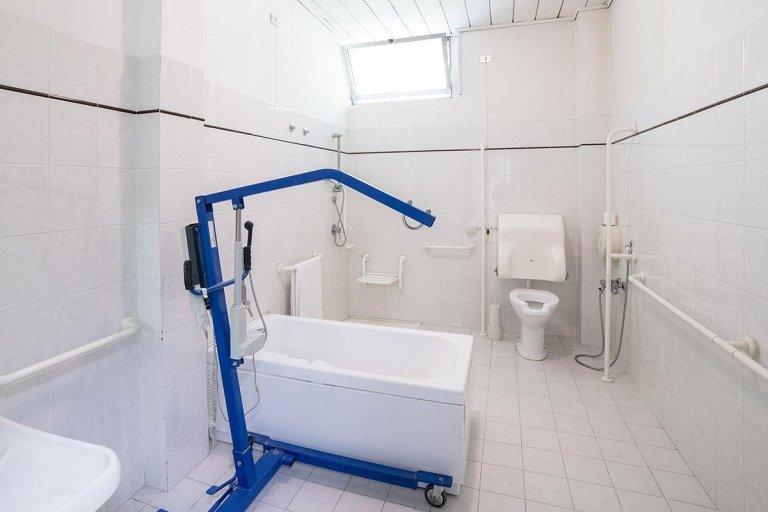 vista frontale di un bagno con bide, lavabo, vasca e asciugamani
