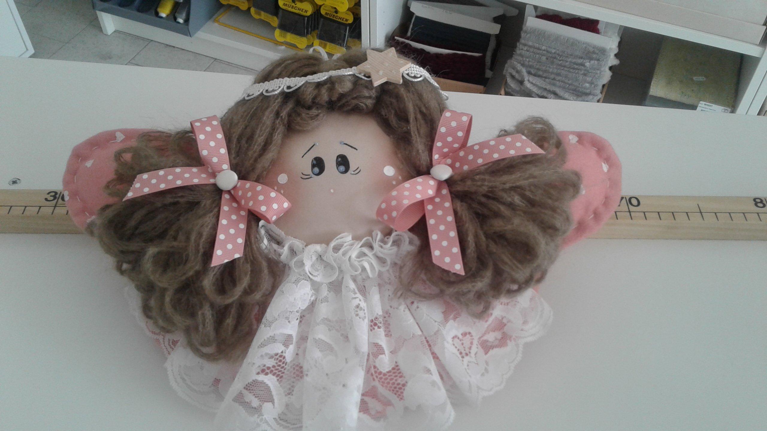 bambola di pezza con fiocco rosa
