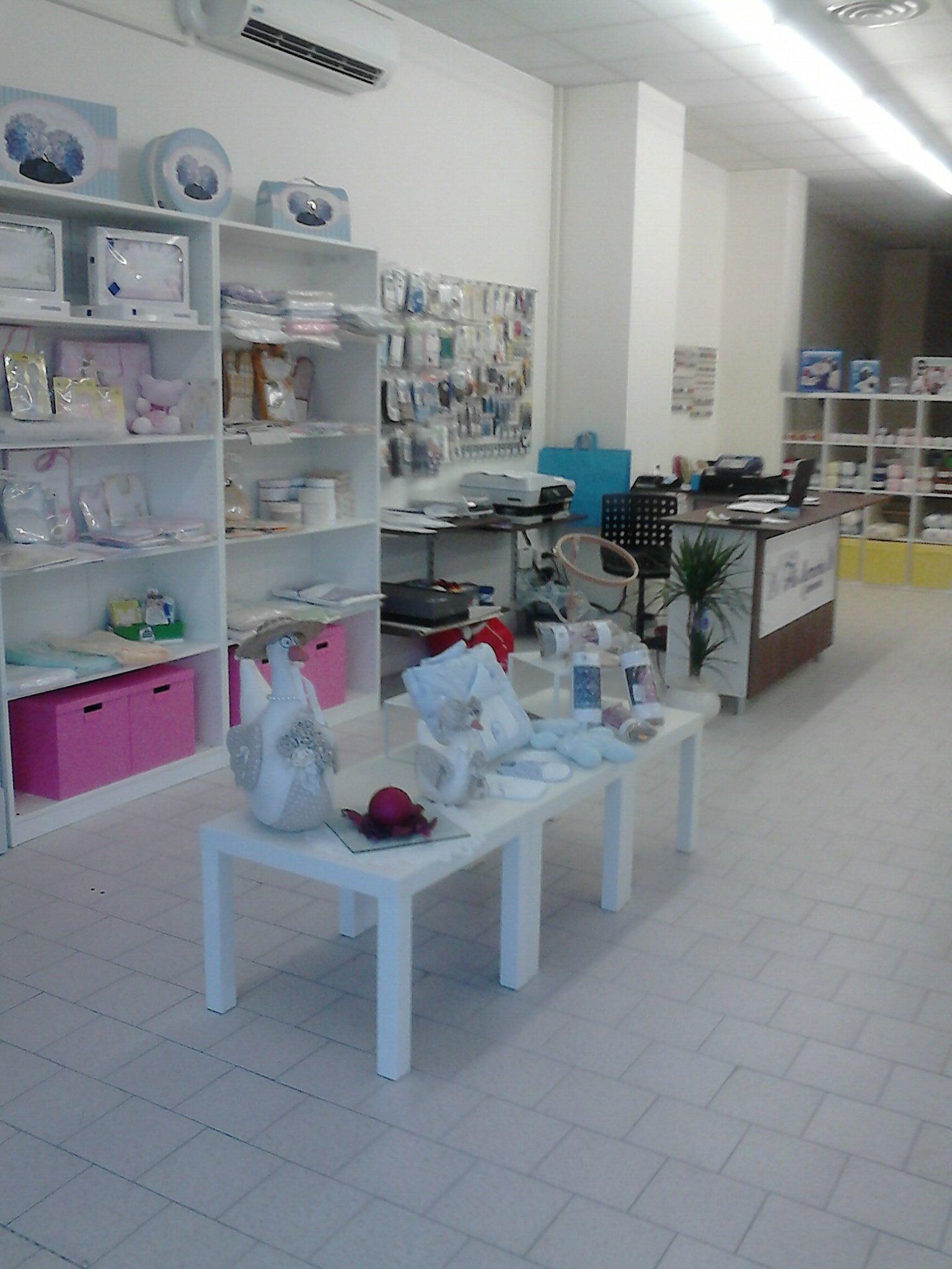 interno del negozio con esposizione lavori di sartoria su scaffali e tavoli