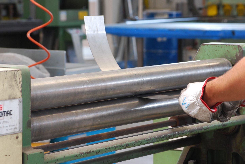 mano di un operaio che tiene una lastra di ferro in mezzo a un rullo di tubi meccanici