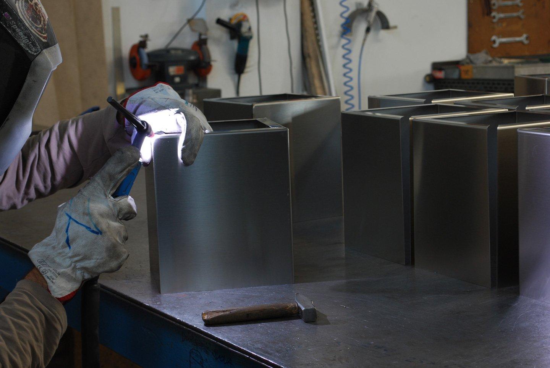 operaio mentre lavora materiali in acciaio inossidabile  in una officina