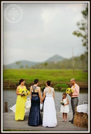 bride and bridesmate with a man and girl standing on the lakeside