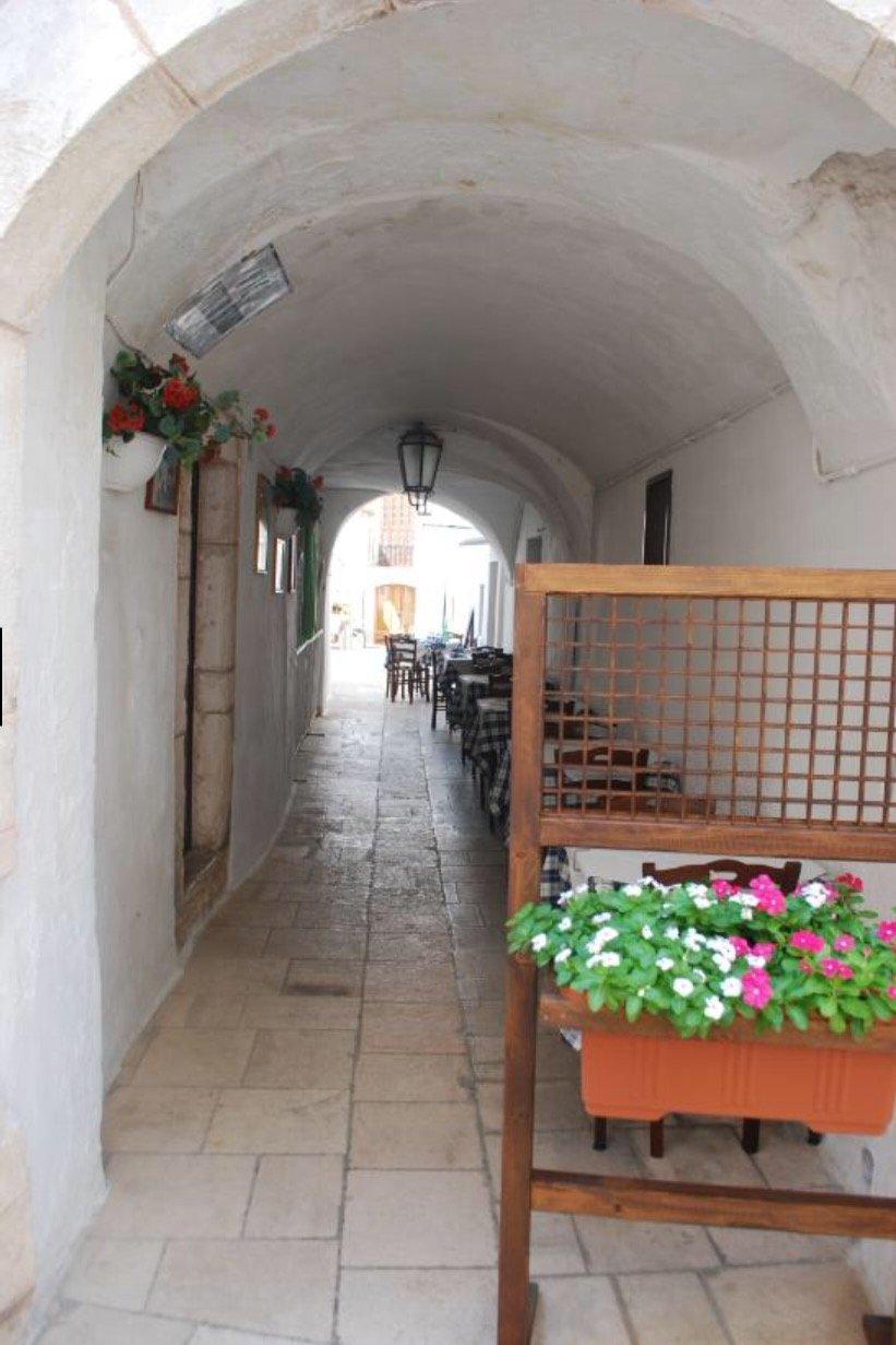 Lungo corridoio con tavoli, Vaso di fiori bianchi e rosa