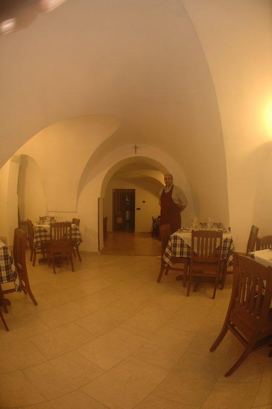 Cameriere all' interno di ristorante, tavoli liberi a Locorotondo, BA
