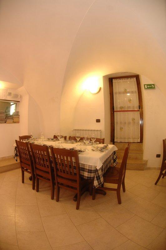 Interno del ristorante, ambiente caldo, Tavola apparecchiata con piatti e bicchieri di vino a Locorotondo, BA