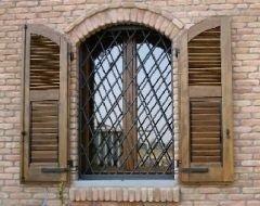 una finestra con una griglia e due persiane in legno aperte