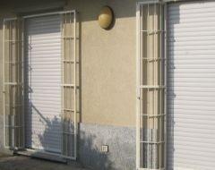 delle finestre con delle tapparelle bianche