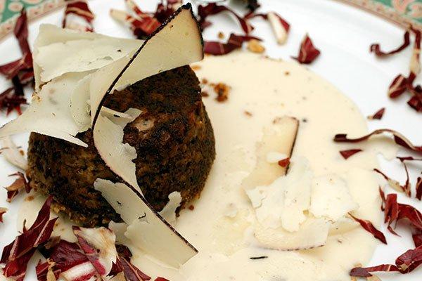 Un piatto di tortino salato con della crema, insalata rossa e scheggia di formaggio grattugiato