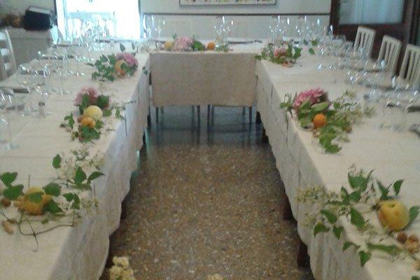 Due tavole lunghe apparecchiati con tovaglia bianca, piatti bicchieri e decorazione con rametti, frutta e fiori