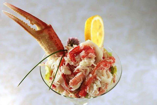 Una coppa di vetro con insalata di pesce e decorazione con una fetta i limone chela di granchio