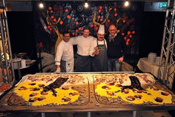 Tre cuochi in camice bianco e grembiule,un altro uomo in una maglia nera abbracciati davanti una torta enorme con disegni di alberi in color giallo e marrone