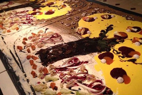 Vista ravvicinata di una torta enorme con dei disegni di alberi realizzati con crema di color giallo e sciroppo di cioccolato
