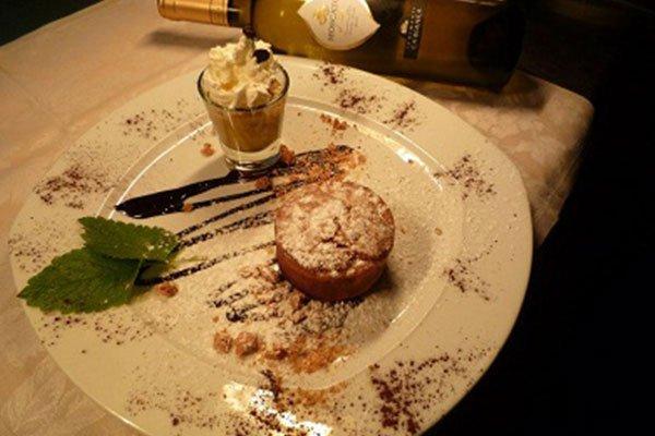 Un piatto con una tortina, un bicchiere di liquore con della crema , decorazioni con zucchero velo e sciroppo di cioccolato