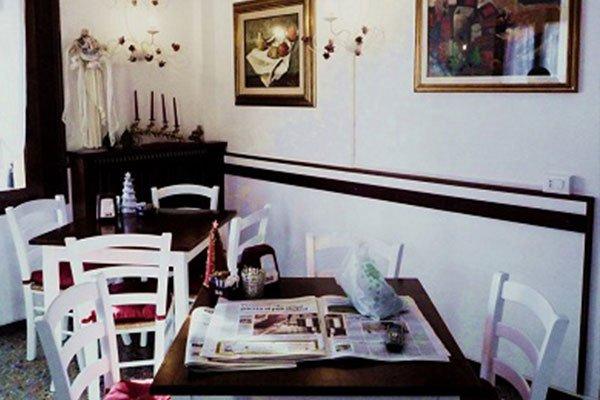 All'interno di un ristorante  Due tavoli con sedie di color bianco, un mobile in un angolo con delle candele e dei quadri appesi sul muro