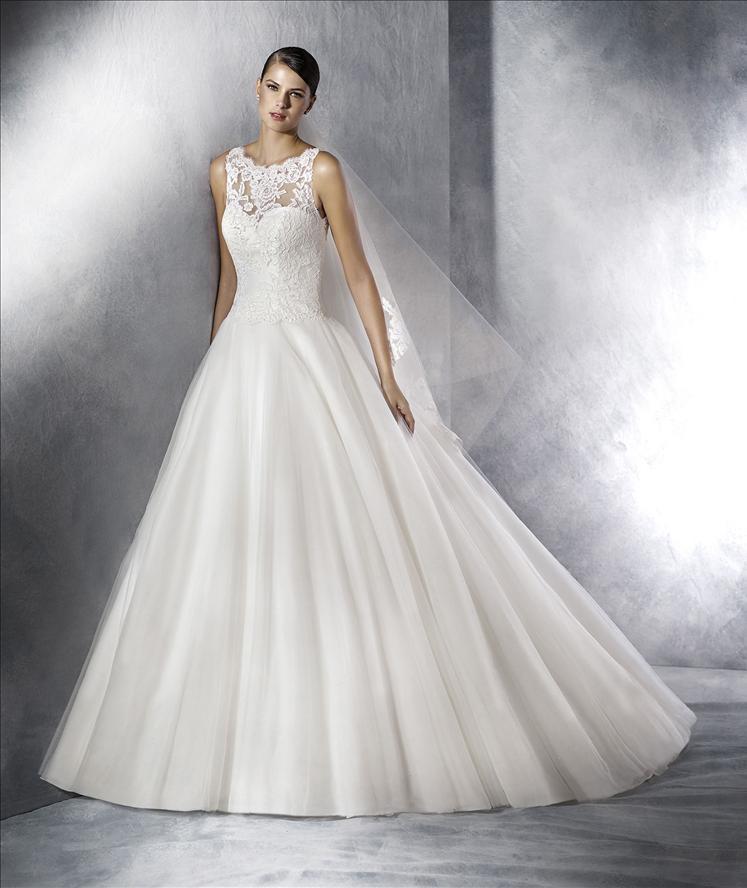 modella in posa e vestita da sposa, appoggiata a un muro