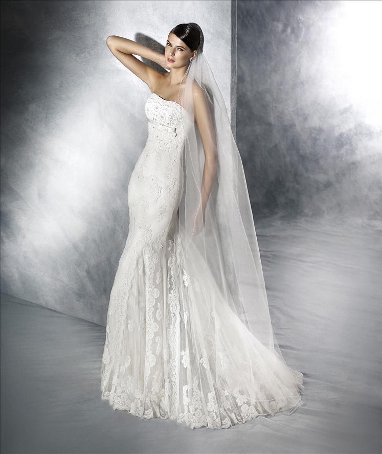 Modella in posa con abito da sposa bianco che si tocca il collo
