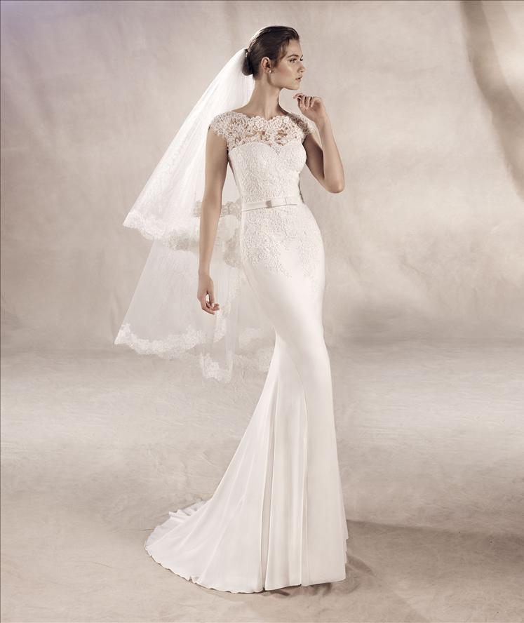 Modella con un vestito da sposa con velo corto