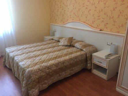 Camera da letto matrimoniale in toni chiari e pavimento in legno
