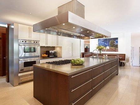 una cucina angolare di color avorio con penisola  e cappa in acciaio inox