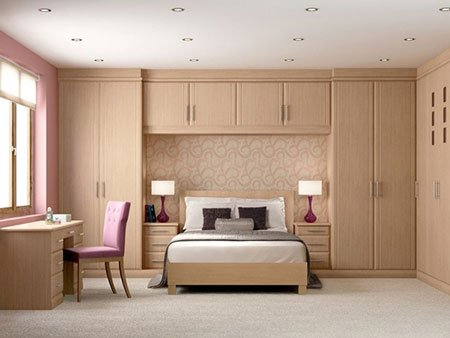 una camera con un letto matrimoniale, armadio e una scrivania in legno chiaro