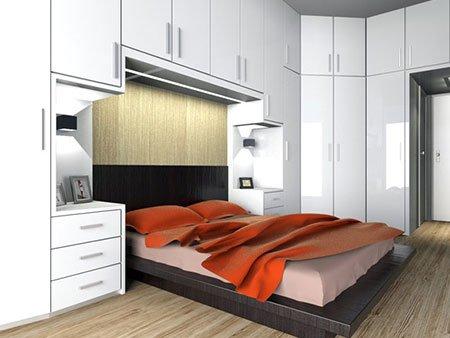una camera con un letto in legno scuro e degli armadi laccati di color bianco