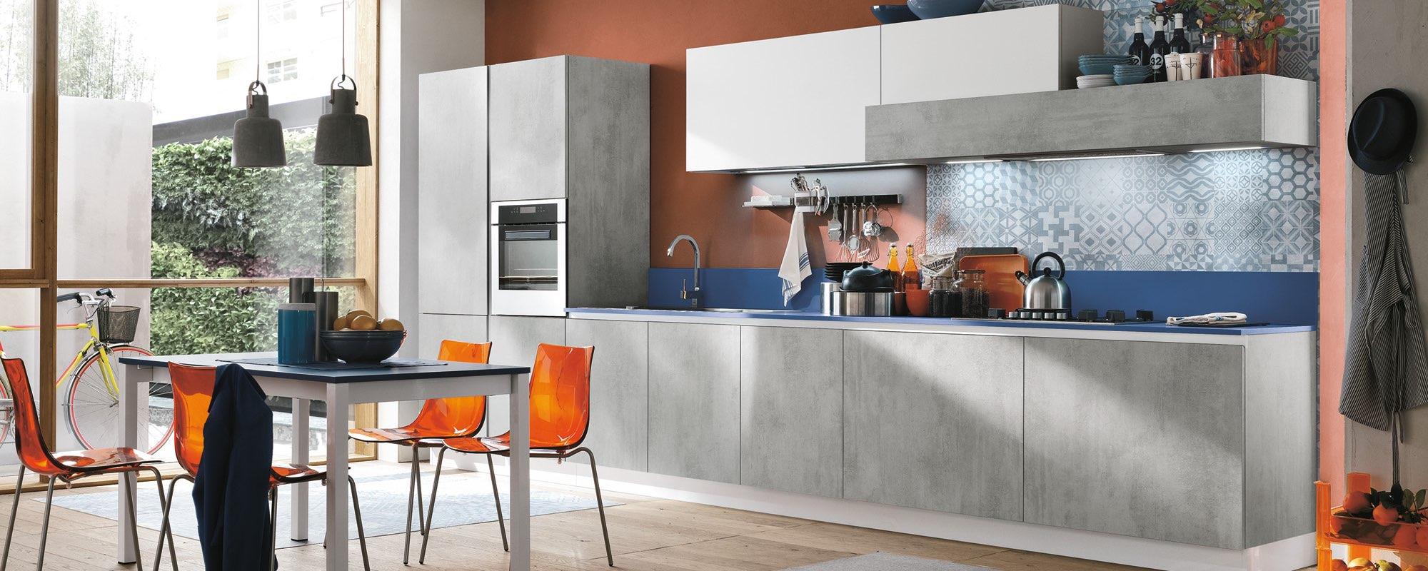cucina con tavolo in mezzo e sedie arancioni