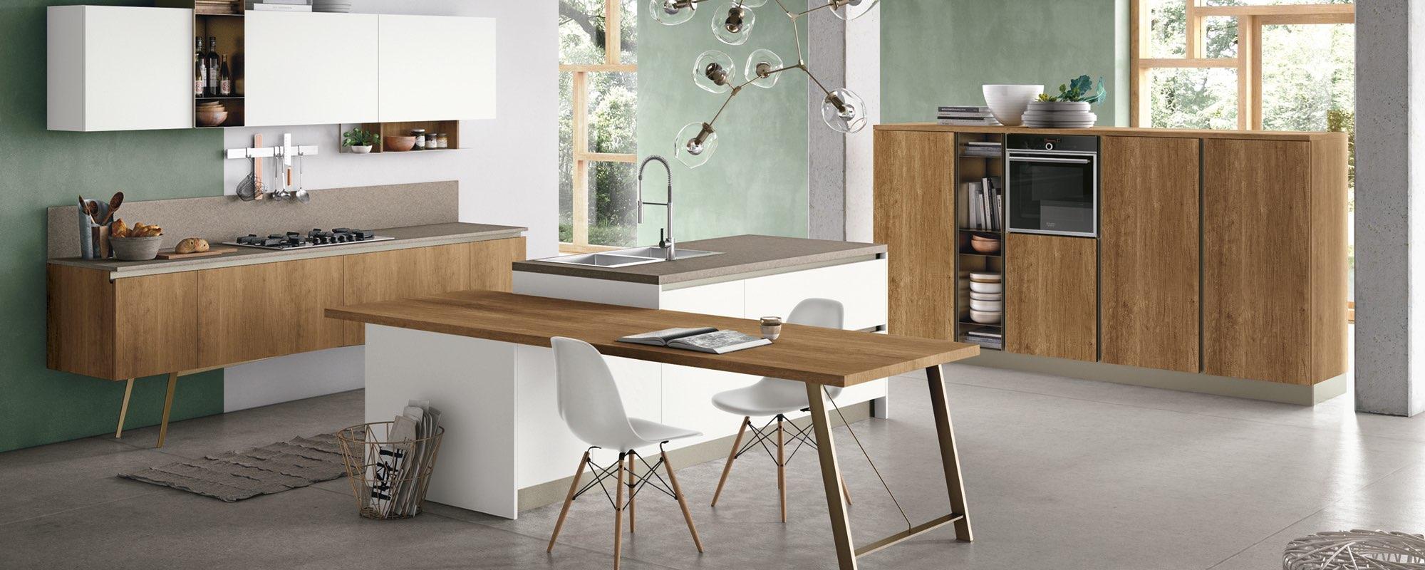 isola con lavandino e tavolo in mezzo alla cucina
