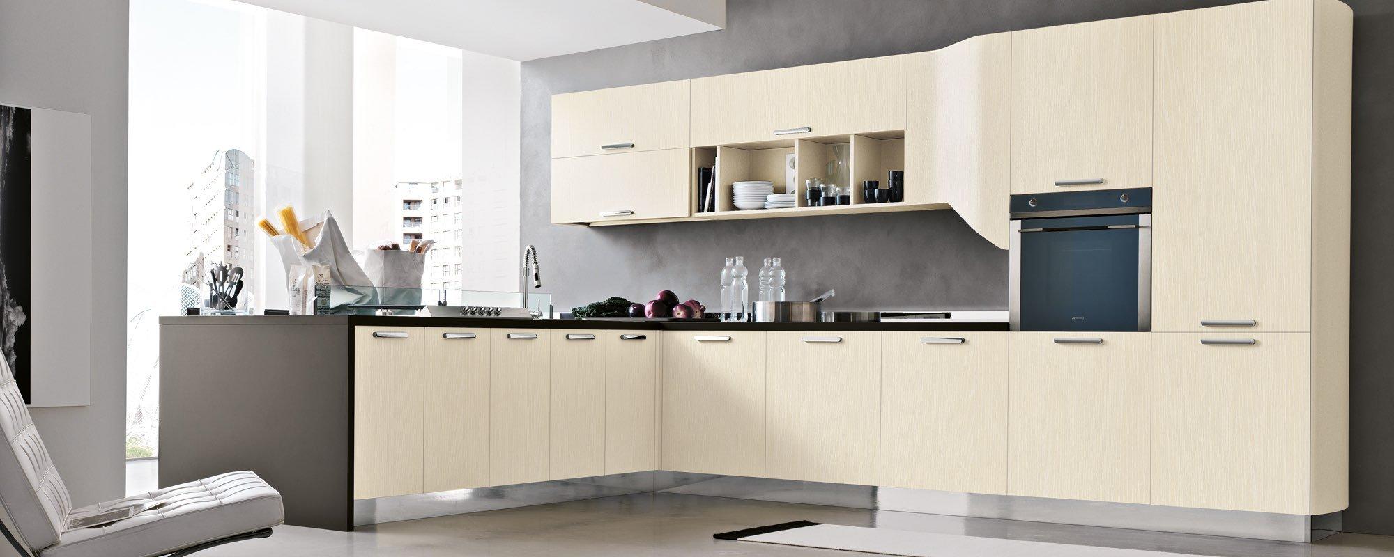 vista angolare di una cucina moderna color crema con piani di lavoro neri, forno incassato -Milly