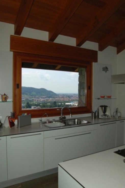 una cucina con mobili bianchi e vista di una finestra