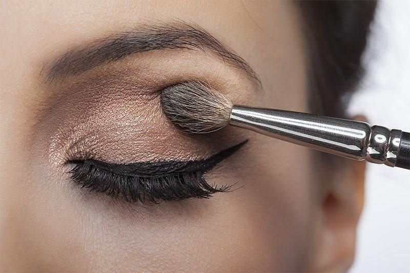 occhio  chiuso con eyeliner e pennello che ritocca l`ombretto nella palpebra