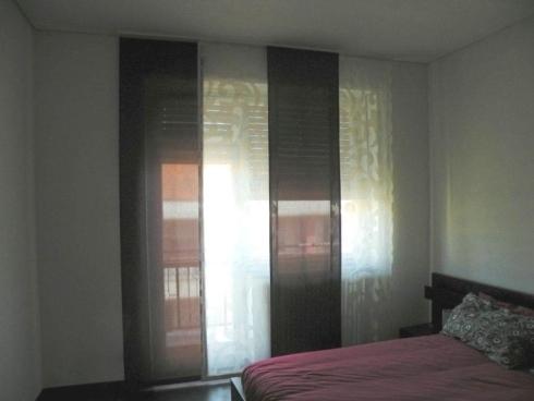 una camera con un letto e delle tende bianche con disegni