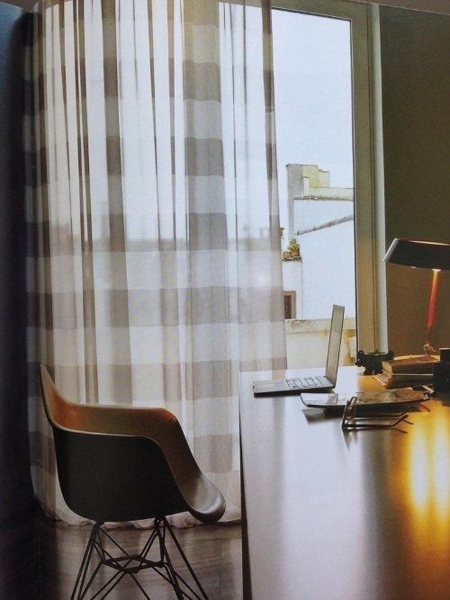 una scrivania, una sedia e delle tende