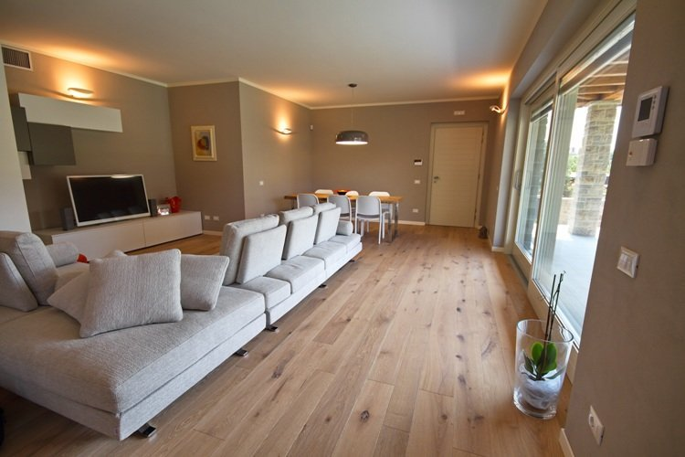 salotto con divano bianco e Parquet rovere vecchio