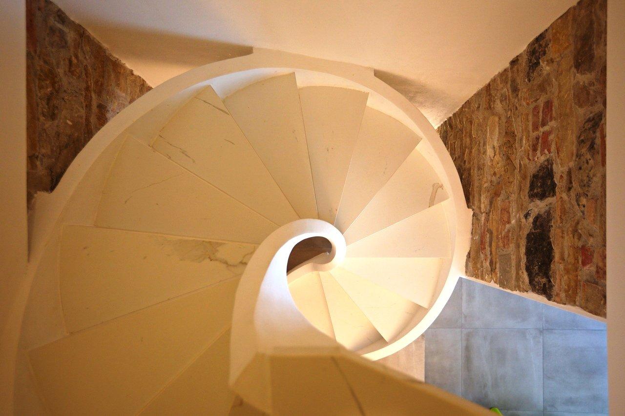 Scala elicoidale in cemento con pedata in marmo bianco