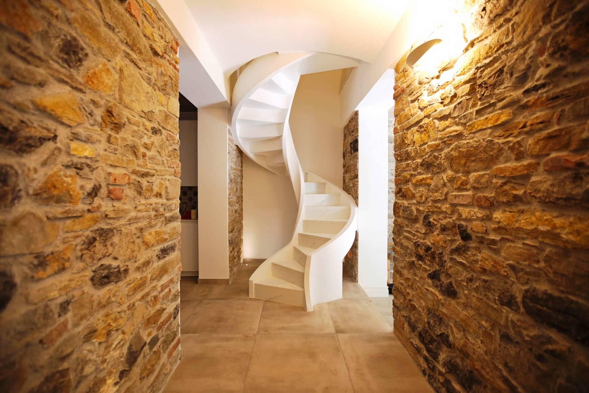 pareti in pietre con una scala interna bianca