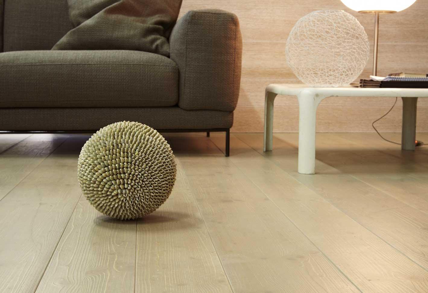 primo piano di un divano con pavimento in legno e oggetti da casa
