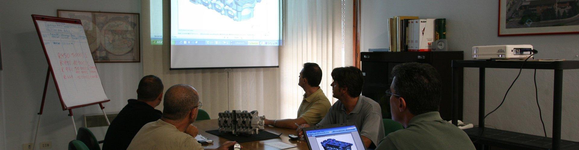 degli uomini seduti in una sala conferenze che osservano un disegno tecnico proiettato su un telo