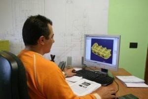 un uomo alla scrivania che osserva il monitor di in computer con un disegno tecnico