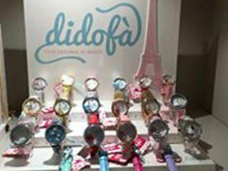 degli orologi di diversi colori e dietro un pannello con scritto Didofà'