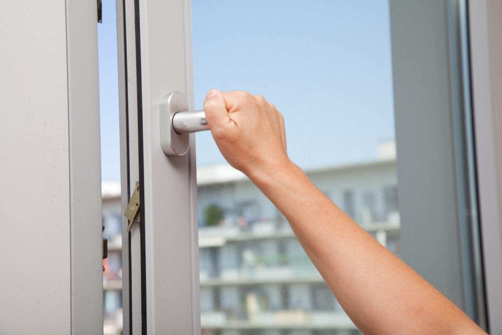Donna stringe la maniglia di una finestra