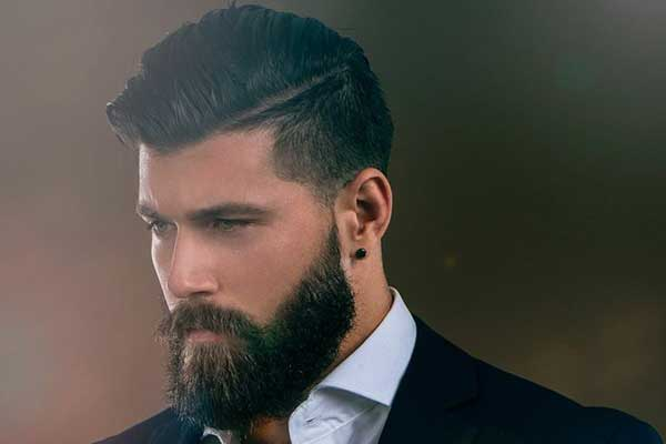 un barbiere con barba e capelli neri sta radendo un ragazzo seduto su una sedia