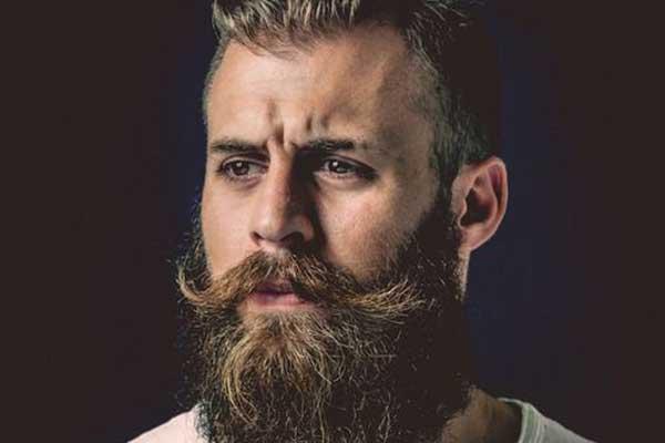 un parrucchiere sta facendo la barba a un ragazzo