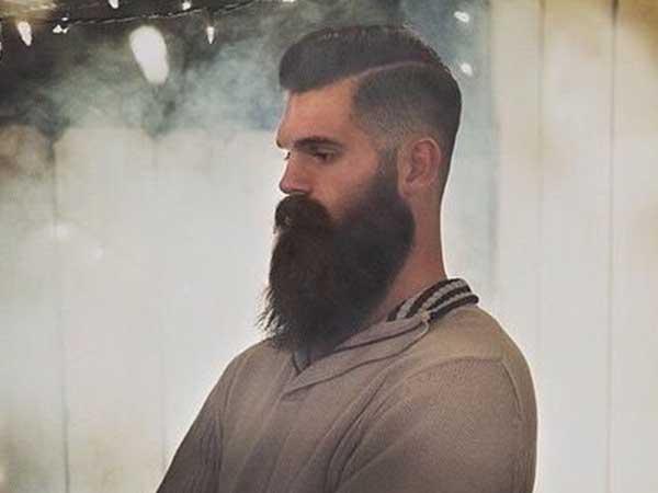 un ragazzo a braccia conserte con capelli appena tagliati e barba indossa un golf beige