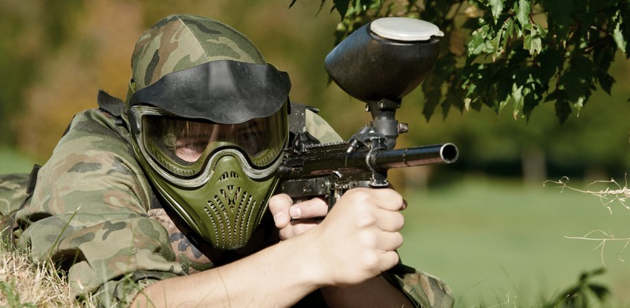 Man in camouflage clothing and goggles, with a paintball gun