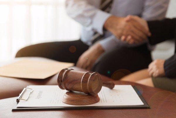 martello da giudice,sullo sfondo due persone si stringono la mano