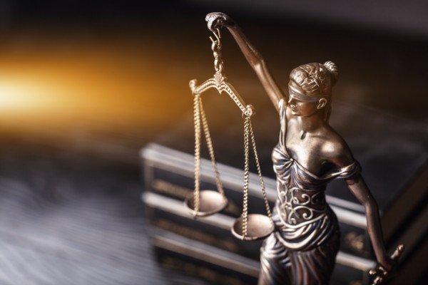 statuetta della dea della giustizia,sullo sfondo libri di  legge