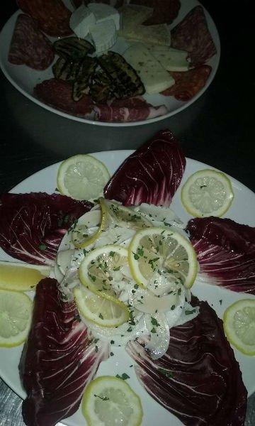un piatto di salumi, formaggi e insalata rossa